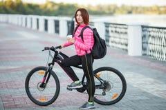 Dorosła piękna rudzielec kobieta pije ranek kawę pozuje na bicyklu w jesieni miasta rzeki molu z koczka ostrzyżenia główkowaniem Obraz Royalty Free