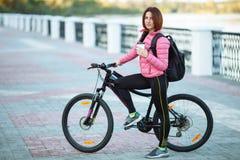 Dorosła piękna rudzielec kobieta pije ranek kawę pozuje na bicyklu w jesieni miasta rzeki molu z koczka ostrzyżenia główkowaniem Zdjęcie Royalty Free