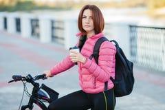 Dorosła piękna rudzielec kobieta pije ranek kawę pozuje na bicyklu w jesieni miasta rzeki molu z koczka ostrzyżenia główkowaniem Zdjęcia Royalty Free