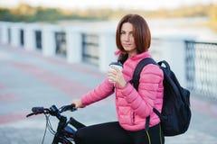 Dorosła piękna rudzielec kobieta pije ranek kawę pozuje na bicyklu w jesieni miasta rzeki molu z koczka ostrzyżenia główkowaniem Fotografia Stock
