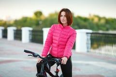Dorosła piękna rudzielec kobieta z koczka ostrzyżeniem pozuje na bicyklu w jesieni miasta rzeki molu Fotografia Stock
