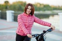 Dorosła piękna rudzielec kobieta z koczka ostrzyżeniem pozuje na bicyklu w jesieni miasta rzeki molu Obraz Stock