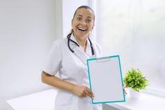 Dorosła uśmiechnięta kobiety lekarka z pustym prześcieradłem na schowku dla twój teksta, tło szpitala okno obraz royalty free