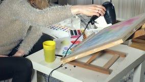 Dorosłe kobiety malują z barwionymi akwareli farbami i suszą z włosianą suszarką w szkole artystycznej