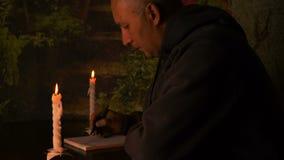 Dorosłe mężczyzna writing notatki w notatniku Świeczki i enigmatyczna atmosfera Mężczyzna obsiadanie przy stołem zbiory