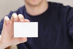 Dorosłego mężczyzna ręki mienia pusta wizytówka przed kamerą obrazy stock