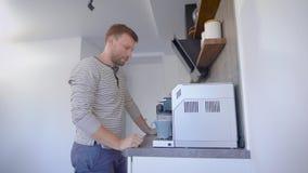 Dorosłego pojedynczy mężczyzna zbliża się kawowa maszyna na jego kuchni w mieszkaniu w ranku stawia jego filiżankę i wyłacza dale zbiory wideo