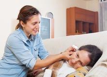 Dorosłej córki kapiący ucho opuszcza jego matka obrazy stock