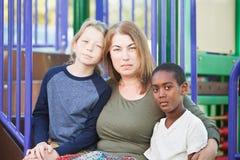 Dorosłej kobiety obsiadanie z dwa chłopiec Zdjęcie Royalty Free