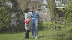Dorosłej kobiety odprowadzenie z koszem z tulipanami w nim na podwórko Dorosły wnuk przychodzi damy i ściska facet zdjęcie wideo
