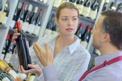Dorosłej kobiety sprzedawcy seansu butelki wino męski klient Zdjęcia Stock