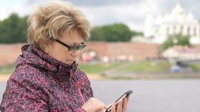 Dorosłej kobiety turysta trzyma smartphone outdoors zdjęcie wideo