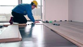 Dorosłej samiec pracownik instaluje laminat podłoga, spławowa drewno płytka zbiory