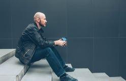 Dorosły łysy brodaty mężczyzna pije kawę od papierowej filiżanki i obsiadanie w schodku przy miasto ulicą zdjęcia stock