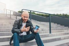 Dorosły łysy uśmiechnięty mężczyzna pije kawę od papierowej filiżanki i używa telefonu komórkowego obsiadanie w schodkach przy mi zdjęcia stock