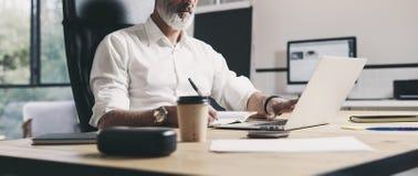 Dorosły biznesmen pracuje przy nowożytnym coworking biurem Ufny mężczyzna używa współczesnego mobilnego laptop szeroki zdjęcia royalty free