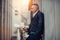 Dorosły biznesmen texting na telefonie komórkowym starannym ścianę na miasto ulicznym pobliskim budynku biurowym Zdjęcie Stock
