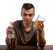Dorosły boozed mężczyzna pokazuje butelkę alkoholiczny napój, odizolowywającą na białym tle Alkoholizmu pojęcie fotografia royalty free