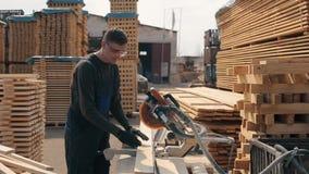 Dorosły cieśli pracownik jest ubranym budowa gogle używać drewnianą tnącą maszynę Mężczyzna ciie drewniane deski zbiory