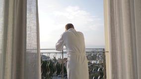 Dorosły mężczyzna w białej wannie iść hotelowy balkon, prostuje jego ręki strona, cieszy się widok 4K zbiory
