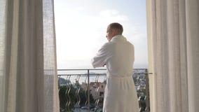 Dorosły mężczyzna w białej wannie iść hotelowy balkon, prostuje jego ręki strona, cieszy się widok 4K zdjęcie wideo