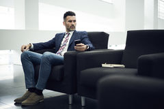 Dorosły mężczyzna w kurtce i szkłach dla rozmowy telefonicza od firma ekonomisty trzyma nowożytnego gadżet fotografia royalty free