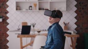 Dorosły mężczyzna w wózku inwalidzkim używać rzeczywistość wirtualna hełm i mieć zbiory