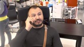 Dorosły mężczyzna z brodą używa telefonu komórkowego smartphone zbiory