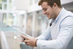 Dorosły męski uczeń używa smartphone w uniwersytecie, zamyka up Zdjęcia Royalty Free