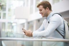 Dorosły męski uczeń używa smartphone w uniwersyteckim wnętrzu Zdjęcie Stock