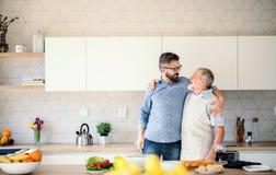 Dorosły modnisia syn indoors i starszy ojciec w kuchni w domu, opowiadający zdjęcia royalty free