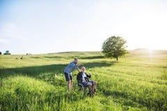 Dorosły modnisia syn z starszym ojcem w wózku inwalidzkim na spacerze w naturze przy zmierzchem obrazy stock