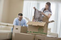 Dorosły pary odpakowania kartony w nowym domu zdjęcia stock