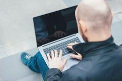 Dorosły pomyślny łysy brodaty mężczyzna w czarnej kurtce używać laptop w schodkach przy miastem obrazy stock