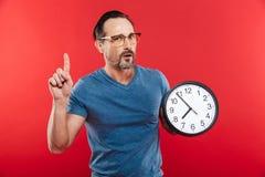 Dorosły poważny mężczyzna mienia zegar zdjęcia royalty free