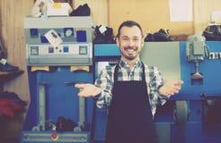 Dorosły pracownik pokazuje jego narzędzia i miejsce pracy Zdjęcia Royalty Free