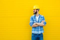 Dorosły pracownik z hełmem na kolor żółty ścianie fotografia royalty free