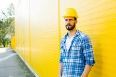 Dorosły pracownik z hełmem na kolor żółty ścianie fotografia stock