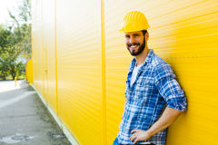 Dorosły pracownik z hełmem na kolor żółty ścianie zdjęcia royalty free