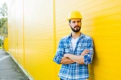 Dorosły pracownik z hełmem na kolor żółty ścianie obrazy stock