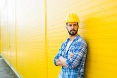 Dorosły pracownik z hełmem na kolor żółty ścianie obraz stock