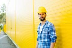 Dorosły pracownik z hełmem na kolor żółty ścianie obraz royalty free