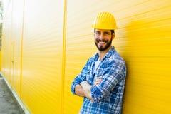 Dorosły pracownik z hełmem na kolor żółty ścianie zdjęcie stock