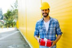 Dorosły pracownik z hełmem na kolor żółty ścianie obrazy royalty free