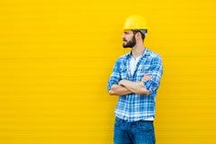 Dorosły pracownik z hełmem na kolor żółty ścianie zdjęcia stock
