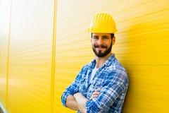 Dorosły pracownik z hełmem na kolor żółty ścianie zdjęcie royalty free