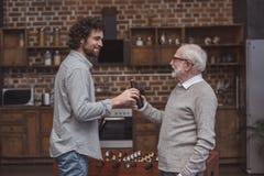 dorosły syn daje starszej ojciec butelce piwo fotografia stock