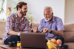 Dorosły syn Pomaga Starszego ojca Z komputerem zdjęcia stock