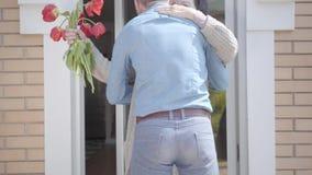 Dorosły wnuk odwiedza jego babci, przynosi jej bukiet tulipany Brodaty mężczyzna ściska jego babci ludzie zbiory wideo