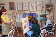 Dorosłych kobiet ucznie siedzą przy sztalugami, studiuje obraz zdjęcie stock